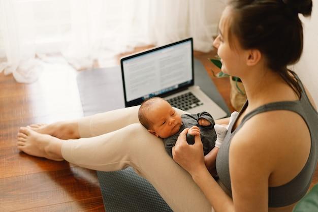 Matka trzyma swojego nowonarodzonego synka i pracuje przy komputerze w domu
