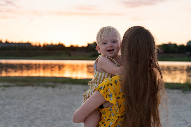 Matka trzyma uśmiechnięte dziecko przed rzeką o zachodzie słońca.