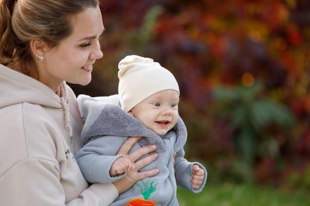 Matka trzyma w ramionach niebieskooki blond chłopiec