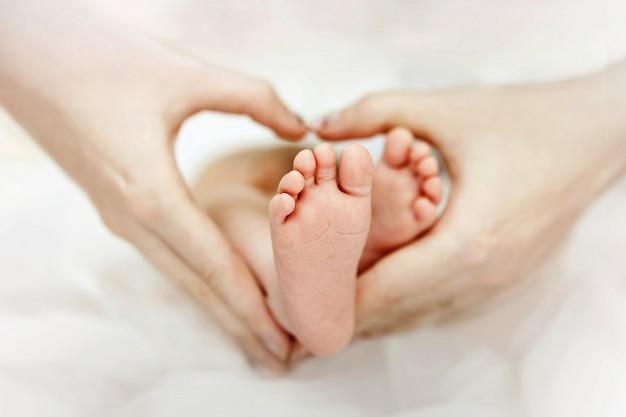 Matka trzyma w rękach stóp noworodka. kształt serca. miłość.