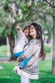 Matka, trzymając córkę i grając w parku w piękny poranek