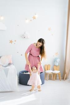 Matka uczy córeczkę chodzić