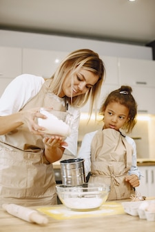 Matka uczy córkę zrobić ciasteczka na blacie kuchennym. kuchnia jest jasna.