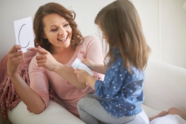 Matka uczy listów córkę