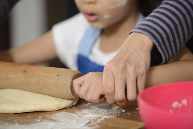 Matka uczy swoją córkę robienia chleba