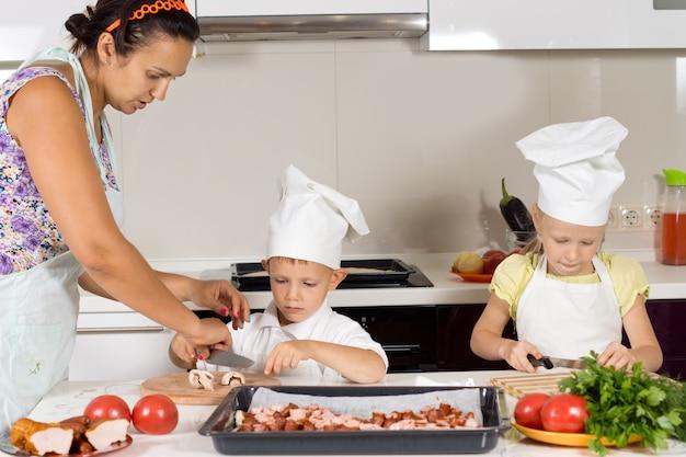 Matka uczy swoje dzieci gotować