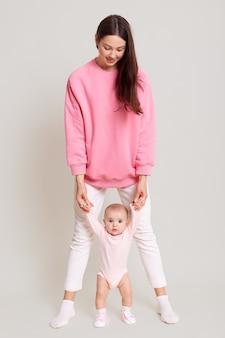Matka uczy swoje małe dziecko chodzić na białym tle nad białą ścianą, ciemnowłosa kobieta ubrana w białe spodnie i różowy sweter, trzymając jej malucha obiema rękami.