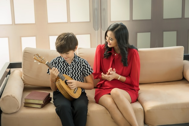 Matka uczy syna, jak grać na gitarze w salonie.