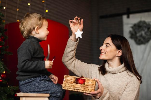 Matka uczy syna, jak ozdobić choinkę