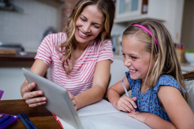 Matka używa cyfrową pastylkę podczas gdy pomagający córki z jej pracą domową