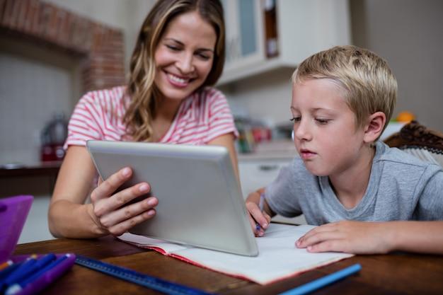 Matka używa cyfrową pastylkę podczas gdy pomagający syna z jego pracą domową