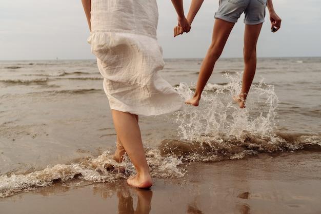 Matka w białej sukni i córka w krótkich nogach spodenki z bliska, skoki do morza z plamami, trzymając się za ręce. zdjęcie wysokiej jakości