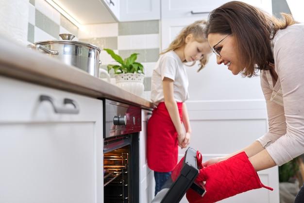 Matka w fartuch i córka mały pomocnik razem przygotowuje babeczki. kobieta wyjmując tacę z pieczonymi babeczkami z piekarnika, wnętrze domu kuchnia. rodzina, dzień matki, zdrowe domowe wypieki