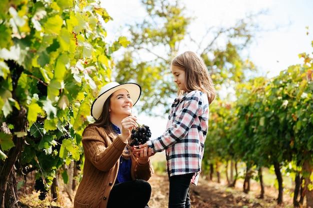 Matka w kapeluszu przedstawia córce czerwone winogrona rodzin hodowców wina