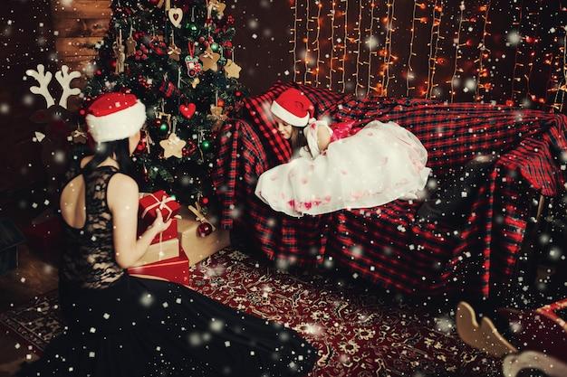 Matka w pięknej czarnej sukience i czapce świętego mikołaja z prezentem przeciwko śpiącemu dziecku na kanapie.