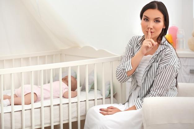 Matka w pobliżu łóżeczka ze śpiącym dzieckiem w domu