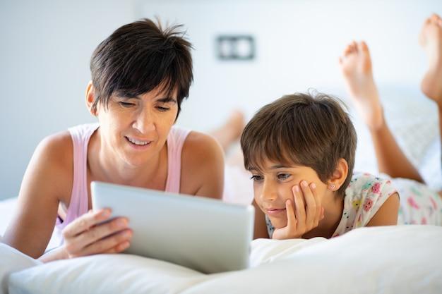 Matka w średnim wieku z ośmioletnią córką za pomocą cyfrowego tabletu w sypialni.
