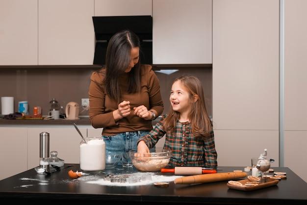 Matka wkłada palcami trochę smaku kremowego ciasta na nos córki i śmieje się