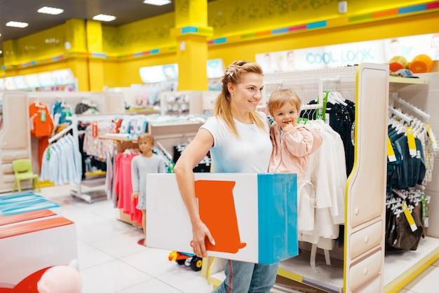 Matka z córeczką kupują w sklepie dziecięcym.