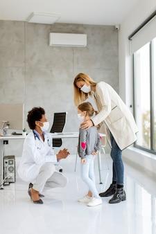 Matka z córeczką podczas badania pediatry przez lekarza afroamerykańskiego