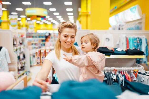 Matka z córeczką wybiera ubrania w sklepie dla dzieci.