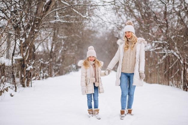 Matka z córką chodzi wpólnie w zima parku
