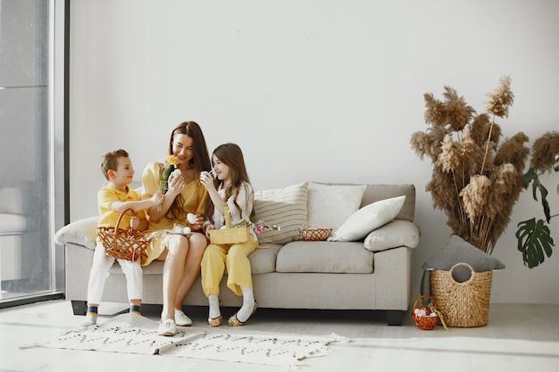 Matka z córką i synem w domu. przygotuj świąteczny koszyk. w odświętnych ubraniach