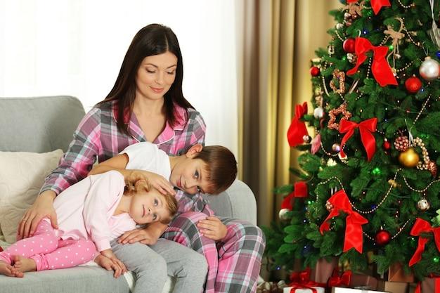Matka z córką i synem w pobliżu choinki