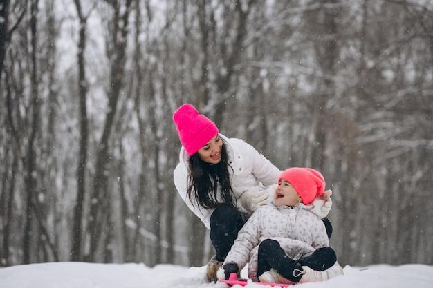 Matka z córką jedzie na talerzu w zima parku