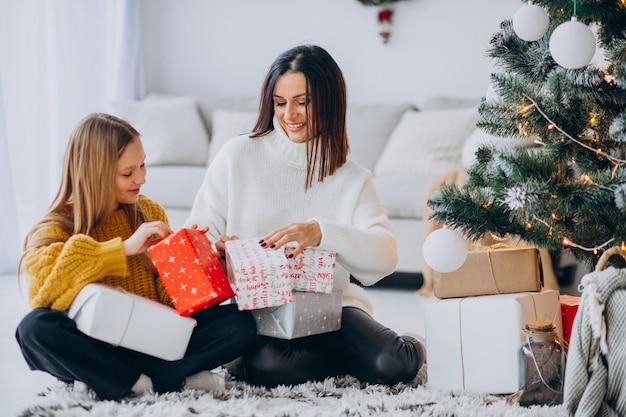 Matka z córką pakowania prezentów pod choinką
