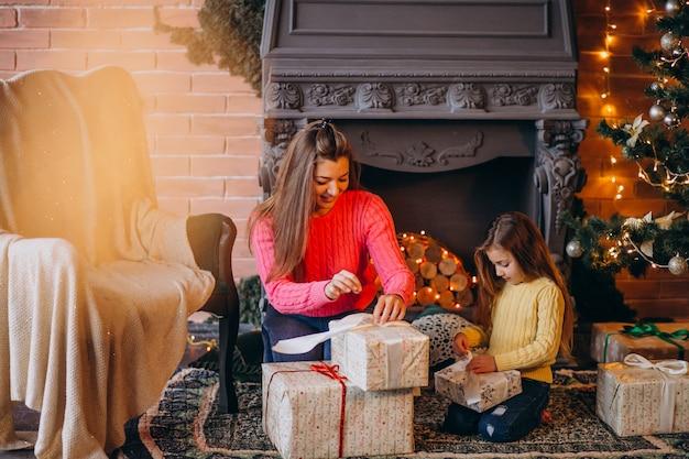 Matka z córką pakowania prezentu przez kominek na boże narodzenie