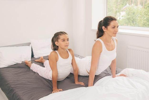 Matka z córką robi joga ćwiczeniu w łóżku
