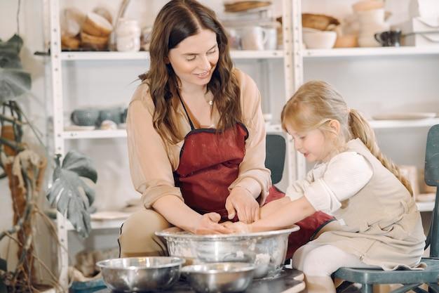 Matka z córką robi wazon w studiu garncarskim
