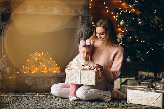 Matka z córką rozpakowywania prezentów przez choinki