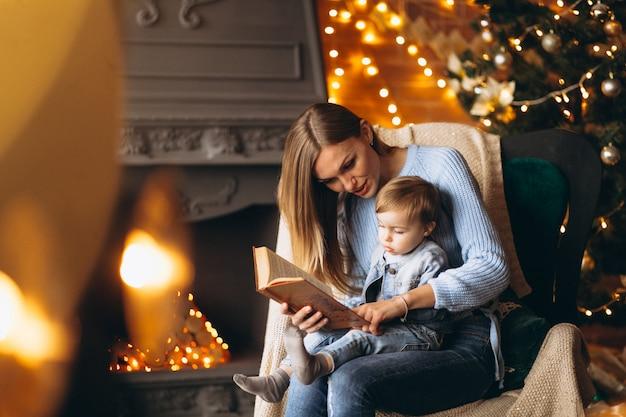 Matka z córką siedzi w fotelu przez choinkę
