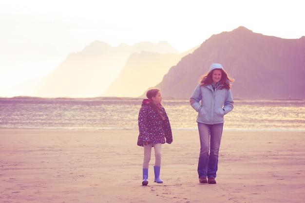 Matka z córką spacerującą po piaszczystej plaży o zachodzie słońca