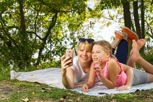 Matka z córką spędza czas ze sobą w lesie, leżąc na zaślepionym i zapierającym dech w piersiach widokiem na staw