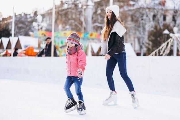 Matka z córką uczy jazda na łyżwach na lodowisku