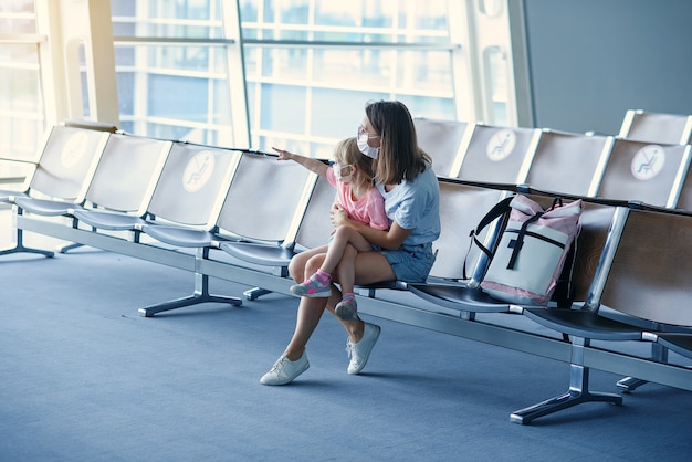 Matka z córką w maskach czekają na lot na lotnisku kobieta z małą dziewczynką w