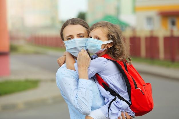Matka z córką w maskach na twarz wracają do szkoły