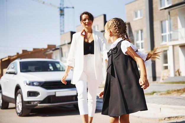 Matka z córką w mundurku szkolnym na zewnątrz w pobliżu białego samochodu.