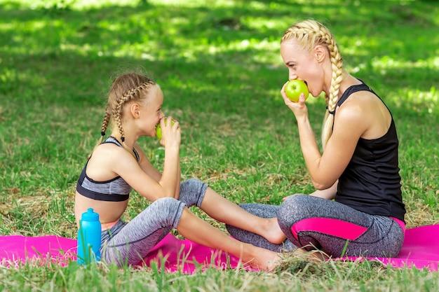 Matka z córką w sportowej zjada jabłka siedząc na macie w parku latem