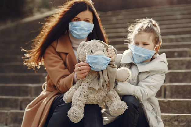Matka z córką wychodzi na zewnątrz w maskach