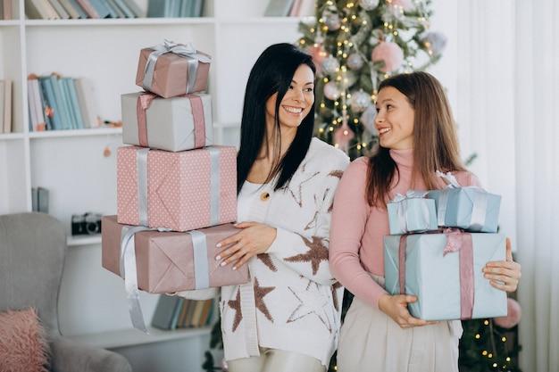 Matka z dorosłą córką z świątecznymi prezentami choinką