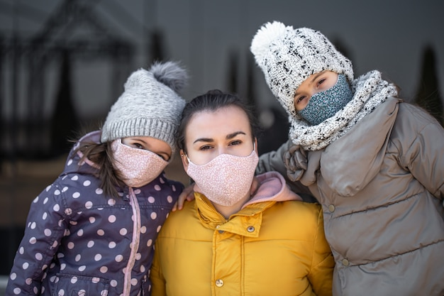 Matka z dwiema córkami w maskach podczas pandemii koronawirusa.