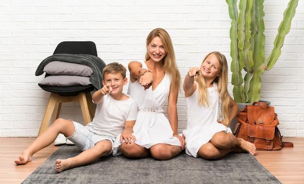 Matka z dwójką dzieci w pomieszczeniu, wskazując na przód