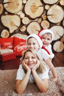 Matka z dwoma synami w czapkach świątecznych leżą w pobliżu drzewa noworocznego w tle ściętych drzew.
