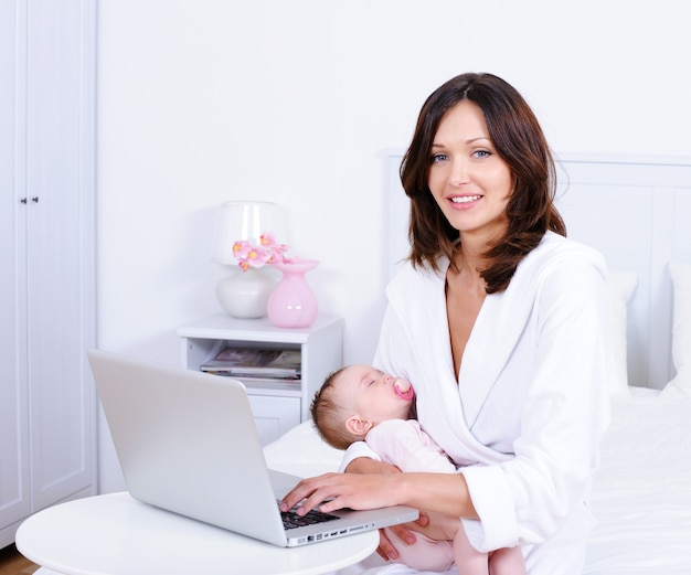 Matka z dzieckiem iz laptopem w domu