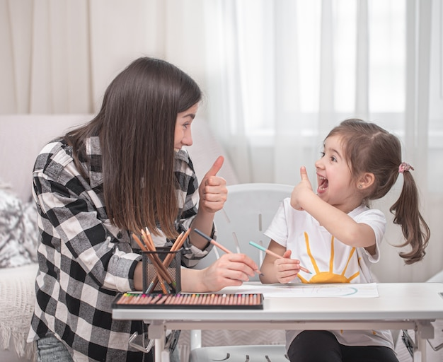 Matka z dzieckiem siedzi przy stole i odrabia lekcje. dziecko uczy się w domu. nauka w domu. miejsce na tekst.