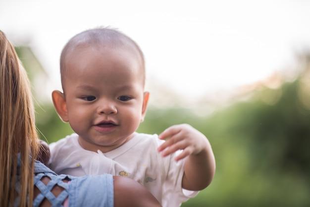 Matka z dzieckiem, śmiejąc się i grając w parku